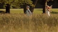 SLO MO TS Girl chasing a boy across a meadow video