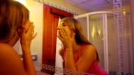 Girl checking her skin in the mirror video