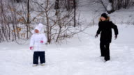 Girl child and teenager boy playing snowballs. Children  in winter park. video
