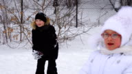 Girl child and teenager boy playing snowballs. Children  in winter park video