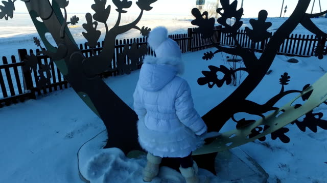 Girl child climbed on a metal tree. Child laughs and rejoices standing on an iron figure. Frosty winter day. video