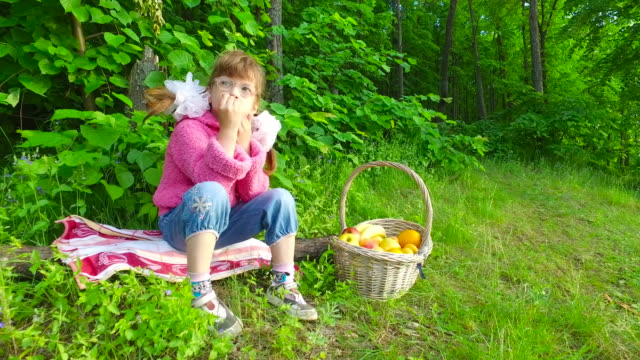 Girl child eats apricots in summer forest. The girl has a good appetite in the fresh air. video