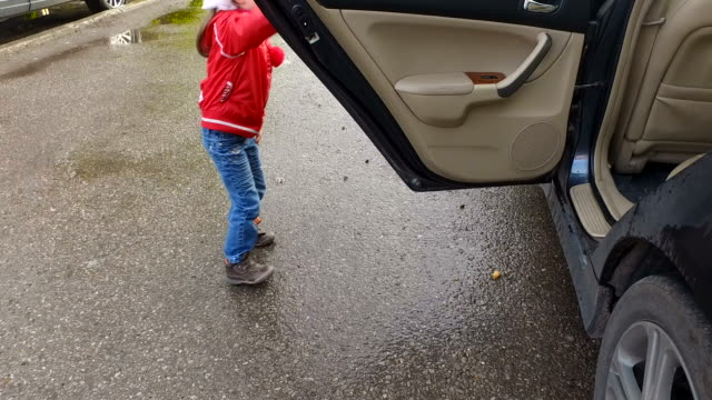 Girl child gets out of the car and then closes the door. video