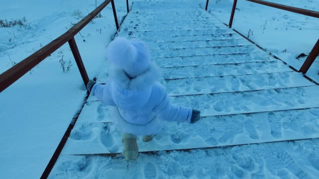 Girl child goes down the stairs covered with snow. Child is walking in the park. Winter frosty day. video