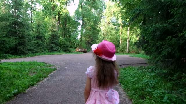 Girl child goes on an asphalt track. The path follows the old park. Summer sunny evening. video