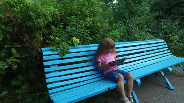 Girl child in glasses enthusiastically working on a tablet computer. Little girl sits on a wooden bench in the park. video
