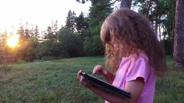 Girl child in glasses enthusiastically working on a tablet computer. Little girl is worth in an evening park. video
