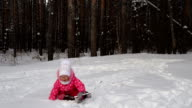 Girl child is learning to ski. But she do not always get and she falls on the snow. Beautiful day in the winter forest video