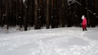 Girl child is learning to ski. She slowly slides on skis in soft fresh snow. Beautiful day in the winter forest video