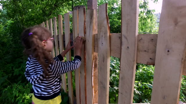 Girl child opens the wooden gate. video