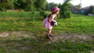 Girl child playing ball on the lawn. In the face of a girl smiling with joy. video