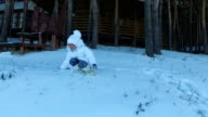 Girl child slides down a hill. The girl's face red from the cold weather. Frosty winter day. video
