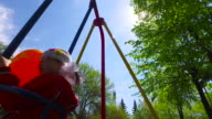 Girl child swinging on a swing. Girl holding a large orange balloon. video