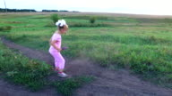 Girl child trains his leg. Little girl trains a kick. She trains on a green meadow. video