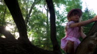 Girl child tries to climb a tree. But she can not. She is still small. video