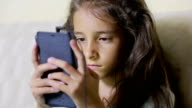 Girl child with a cell phone browses the Internet. headphones video
