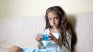 Girl child with a cell phone browses the Internet video
