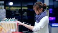 Girl chooses products with a tablet in supermarket video
