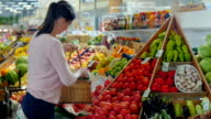 Girl chooses vegetables in a supermarket . video