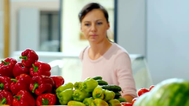 Girl chooses vegetables in a supermarket . video