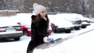 Girl cleans his car from the snow. video