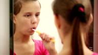 Girl cleans teeth opposite a mirror video