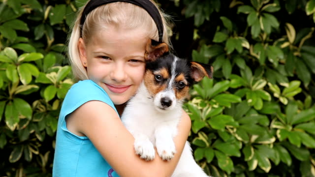 Girl cuddling a puppy outdoors in the garden video