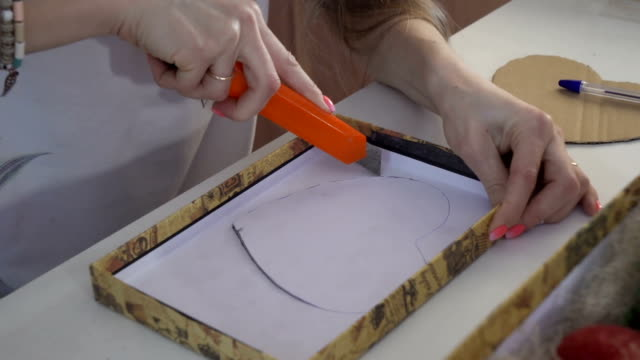 Girl cuts the heart out of cardboard stencil video