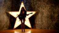girl dancing and posing with electric guitar, shining star in the background. slow motion, silhouette video