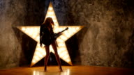 girl dancing with electric guitar, shining star in the background. slow motion, silhouette video