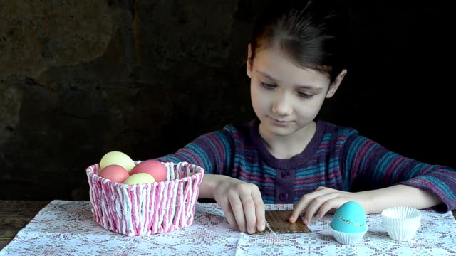 Girl decorated eggs for Easter, and puts in the stand video