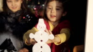 Girl decorates a window with the help of artificial snow. Preparing for the New Year and Christmas. video