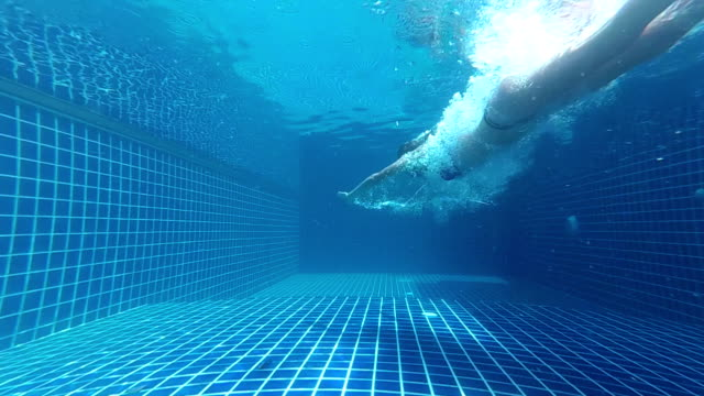A girl dives into the pool. Underwater view. video