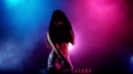 Girl DJ dancing develop her hair behind her multicolored lights and smoke. Silhouette video