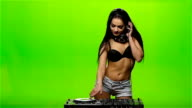 Girl DJ spins the turntable and listening to music on headphones. Slow motion video