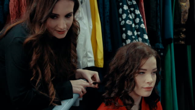 Girl does hairstyle for her girlfriend using hair. video
