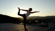 CLOSE UP: Girl doing lord of the dance yoga pose on top of skyscraper at sunrise video