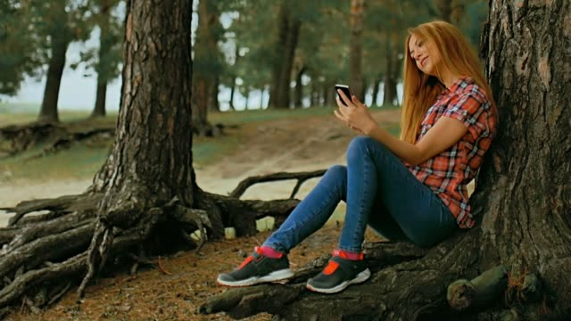 girl doing selfie on phone smartphone sitting in  tree slow motion outdoors video