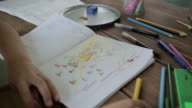 Girl drawing sun on notebook video