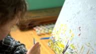 Girl draws paints on canvas video