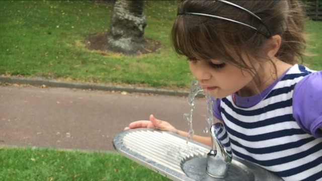 Girl drink water from drinking fountain video