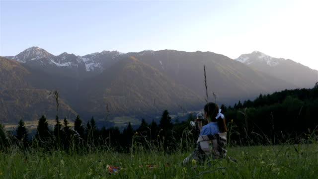 Girl drink whine on the picnic in the alps video