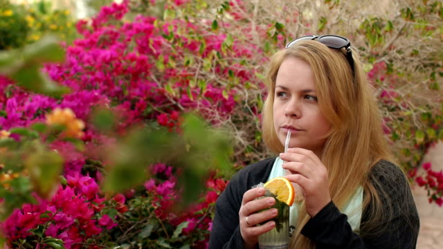 Girl drinking cocktail from the straw in the Park. video