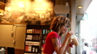 Girl drinking coffee at coffee shop video