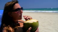 Girl drinking from a coconut on the beach video