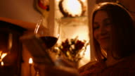 Girl drinking wine by the fireplace in the new year video