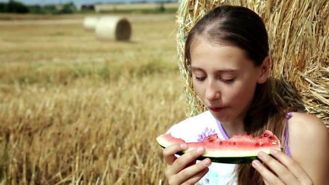 Girl eat watermelon near the haystack video
