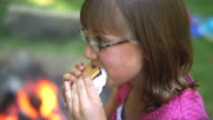 Girl eating a smore by campfire video