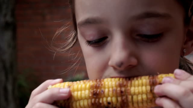 Girl eating grilled corn video