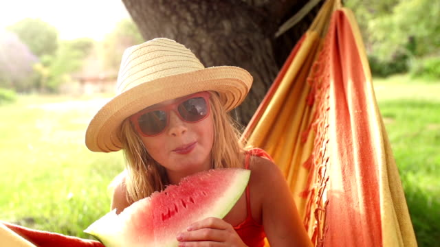 Girl eating slice of watermelon in slow motion video